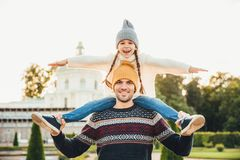 Young handsome father gives piggyback to his little smiling daughter, have fun together when have excursion. Small child looks at royalty free stock image