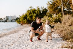 Young Father and His Cute Little Boy Son Walking and Enjoying the Nice Outdoor Weather on the Sandy Beach next to the Ocean Bay royalty free stock image