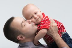 Young handsome father kissing his toddler son. Closeup portrait of young handsome Caucasian father kissing his adorable toddler son, isolated on white stock photography