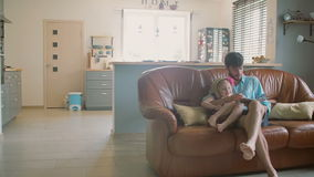 A young handsome father is sitting on the sofa reading a storybook to his precious daughter. Slow mo, Steadicam shot stock footage