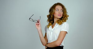 Young handsome female model holds eyeglasses in her hands and poses for a picture. stock video footage