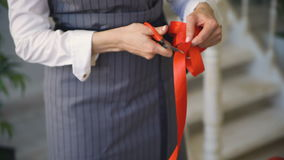 Young handsome florist cut craft ribbon for packing bouquet in studio closeup. Young handsome florist cut craft ribbon for packing bouquet in studio indoors stock footage