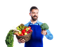 Young handsome gardener. In blue apron. Studio shot on white background Stock Photography