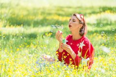 Pretty girl siiting on grass. Young handsome girl sitting on grass and blowing soap bubbles in the air at sunny day in park Stock Photography
