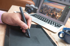 Young Handsome Graphic designer using graphics tablet to do his. Work at desk stock photo