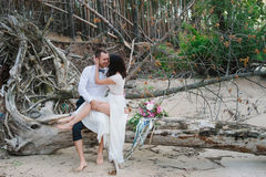 Young handsome groom holds his bride in his arms on the beach with a big bouquet of beautiful flowers Stock Photography