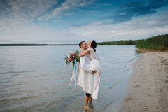 Young handsome groom holds his bride in his arms on the beach with a big bouquet of beautiful flowers Stock Photos