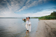 Young handsome groom holds his bride in his arms on the beach with a big bouquet of beautiful flowers Royalty Free Stock Photography