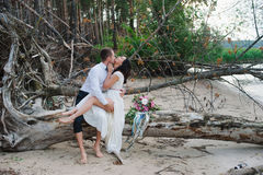 Young handsome groom holds his bride in his arms on the beach with a big bouquet of beautiful flowers Royalty Free Stock Images