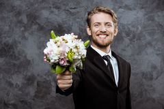 Young handsome groom smiling, holding bridal bouquet over grey background. Stock Photography