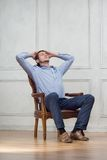 Young handsome guy in arm-chair Stock Images