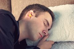 Young handsome guy is asleep wearing black t-shirt. Close up portrait. Day rest, Siesta. yellow ear plugs in the ears of men royalty free stock photos