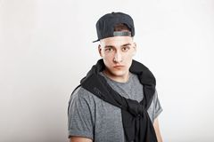 Young handsome guy in a baseball cap with a gray shirt on. A white background royalty free stock photography