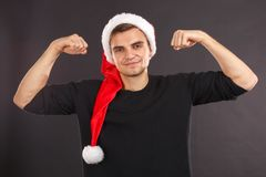 A handsome guy in a black sweatshirt and a Santa hat is showing the biceps and smiling. On a black background. Indoors. A young and handsome guy in a black Royalty Free Stock Image