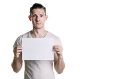 Young handsome guy with a blank sheet of paper, looking surprised at the shot. Place for signature, text. Horizontal frame Royalty Free Stock Images