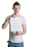 Young handsome guy with a blank sheet of paper, looking surprised shot. Place for signature, text. Vertical frame Royalty Free Stock Photos