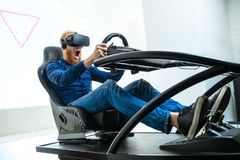 A young, handsome guy, in a blue sports suit, plays in the race, on a simulator of virtual reality stock photos