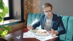 Young handsome guy is at business lunch, using smartphone, sitting at table in cafe, eating tasty food, looking at phone. Screen, holding device in hand in stock video footage