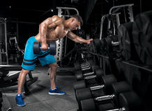 Young handsome guy doing exercises in the gym Stock Image