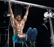 Young handsome guy doing exercises in the gym Stock Photos