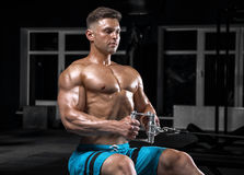 Young handsome guy doing exercises in the gym Stock Images
