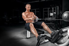 Young handsome guy doing exercises in the gym Royalty Free Stock Images