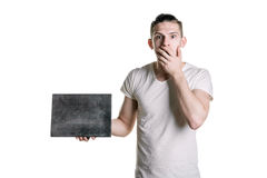 A young handsome guy with an empty gray plank, looks surprised at the shot. Place for signature, text. Horizontal frame Stock Images