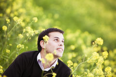 Guy on field. Young handsome guy on field showing hopeful facial expression Stock Photo