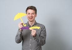 Man holding paper symbols. Young handsome guy holding cardboard blue model of cars and yellow umbrella. Concept for vehicle insurance Royalty Free Stock Photos