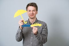 Man holding paper symbols. Young handsome guy holding cardboard blue model of cars and yellow umbrella. Concept for vehicle insurance Stock Image