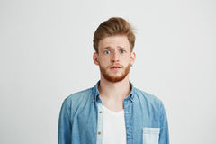 Young handsome guy looking at camera naively hopefully over white background. Royalty Free Stock Images