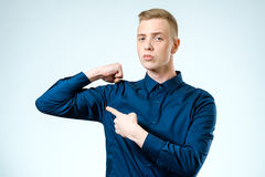 Young handsome guy pointing at his biceps Stock Photos