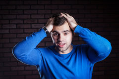 Young  handsome guy scared. A young frightened boy kept hold of the person Royalty Free Stock Photo