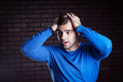 Young  handsome guy scared. A young frightened boy kept hold of the person Stock Photos