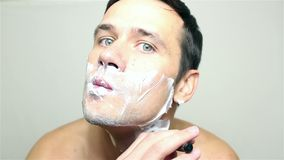 Young handsome guy shaves his face with a razor. Portrait on white background stock video footage