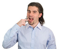 Young handsome guy shows that he wants to eat. Young dark haired man in light blue striped shirt points at his open mouth showing that he wants to eat isolated Stock Images