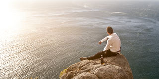 Young handsome guy sitting on rock above ocean Stock Photography