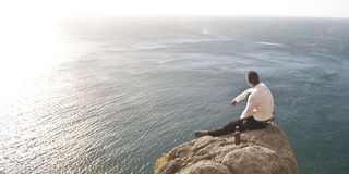 Young handsome guy sitting on rock above ocean Stock Image