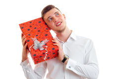 Young handsome guy smiling in shirt keeps near ear big box with gift Stock Photo
