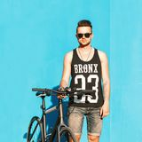 Young handsome guy in sunglasses, a black T-shirt and denim shor. Ts riding a bicycle.on the background of a blue wall Stock Photos