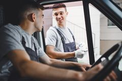 A young handsome guy wearing uniform is looking out of the car window. Another worker wearing uniform is holding the royalty free stock photos