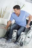 Young handsome handicapped man going from wheelchair to sofa stock image