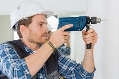 Young handsome handyman using drill at work. Young handsome handyman using a drill at work Royalty Free Stock Photography
