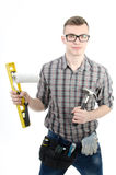 Young handsome handyman. White background. A handsome man in studio. Tools and businesslike. Serious and with a smile Stock Image