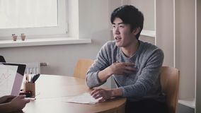 Young handsome happy Japanese man talking by the table, smiling at job interview in modern trendy light office. stock video