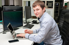 Young handsome happy man with computer in the office. Programmin royalty free stock photos