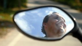 Young handsome happy man drives the motorcycle in jungle road, his face reflected in mirror. Close up. 1920x1080. Young handsome happy man drives the motorcycle stock video footage