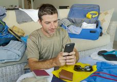 Young handsome and happy man packing travel suitcase at home sofa couch using mobile phone organizing holidays trip booking online. Smiling cheerful in summer Royalty Free Stock Image