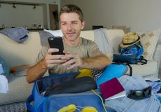 Young handsome and happy man packing travel suitcase at home sofa couch using mobile phone organizing holidays trip booking online. Smiling cheerful in summer Royalty Free Stock Photography