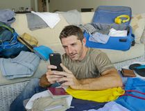 Young handsome and happy man packing travel suitcase at home sofa couch using mobile phone organizing holidays trip booking online. Smiling cheerful in summer Royalty Free Stock Images